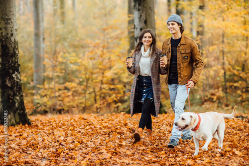 Obraz Family and hot autumn drink, couple in love holding cups of tea or coffee and holding hands, walking with dog. - fototapety do salonu