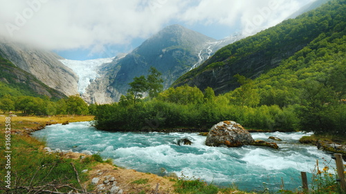 Fototapeta Wide lens shot: Briksdal glacier with a mountain river in the foreground. The amazing nature of Norway obraz