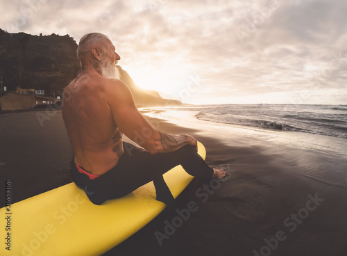 Happy fit senior man sitting on surfboard watching sunset time - Mature bearded surfer having fun on surfing day - Extreme sport and health people lifestyle concept - 316533161