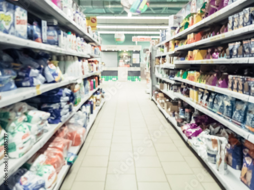 Abstract blurred supermarket aisle with colorful shelves and unrecognizable cust Wallpaper Mural
