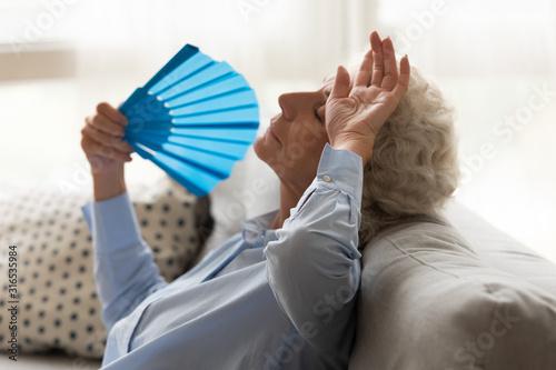 Fototapeta Exhausted older woman feeling unwell, suffering from heat, waving fan obraz