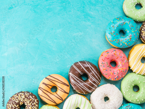 Tablou Canvas Top view of assorted donuts on blue concrete background with copy space