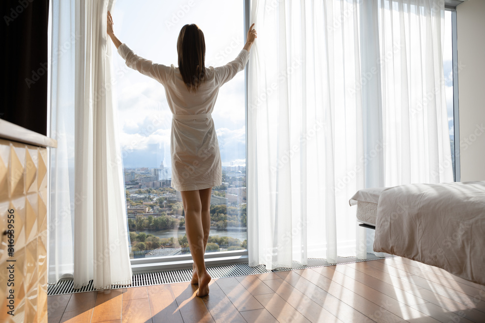 Obraz Rear view beautiful woman starting new day, opening curtains fototapeta, plakat