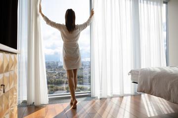 Fototapeta na wymiar Rear view beautiful woman starting new day, opening curtains