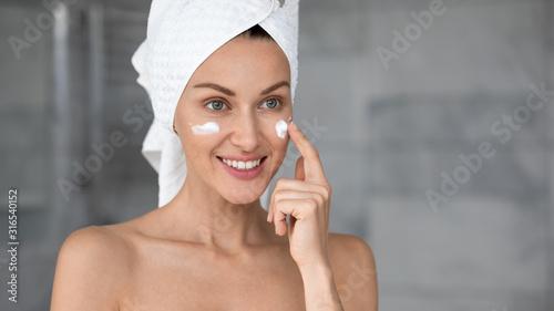 Slika na platnu Head shot smiling beautiful woman with perfect skin applying cream