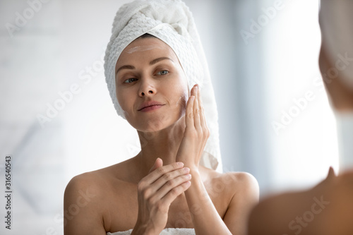 Fotografie, Obraz Head shot beautiful peaceful woman applying moisturizer on face