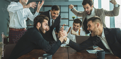 Obraz playful caucasian business people at work place in office, two men play arm wrestling, while colleagues support and cheering them - fototapety do salonu
