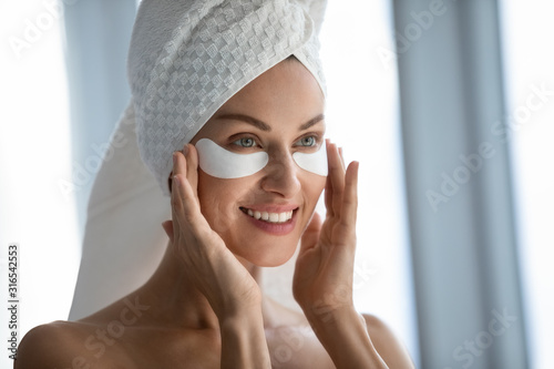 Obraz na plátně Head shot smiling beautiful woman applying hydrogel eye patches