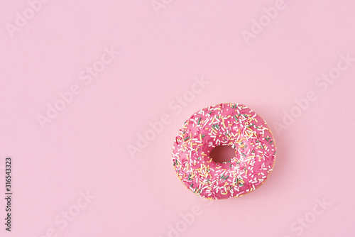 фотография donats decorated sprinkles and icing on a pink background