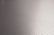 Aluminum surface with many notch spots. Abstract dark gray metallic background or wallpaper. Rows of points go into the distance and form a perspective. Macro