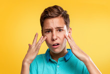 Cosmetology, Dermatology And Acne. A Caucasian Teenager In A Blue T-shirt Is Upset About The Appearance Of Acne. Yellow Background. Copy Space