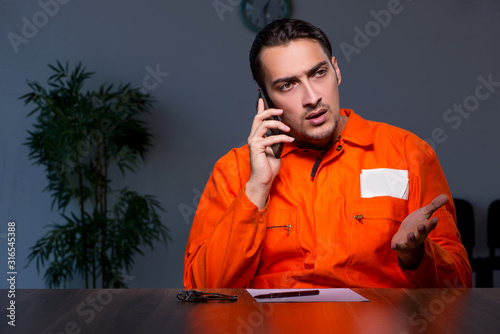 Photo Young convict man sitting in dark room