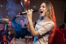 Blond Female Emotionally Sing In Microphone In Karaoke Bar While Friends Celebrating And Having Fun In The Background