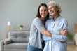 canvas print picture - Happy grandmother and granddaughter hugging, standing in living room