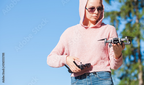 Fototapeta A young woman in a pink hoodie and dark glasses holds drone with one hand, and holds the control panel in the other