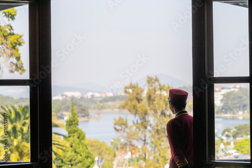 hotel bellboy in french colonial uniform looking out to view of alpine lake and Tapéta, Fotótapéta