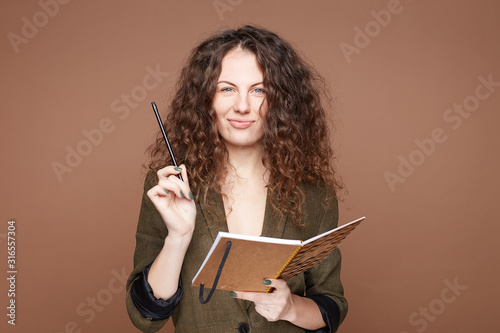 Curly headed blue eyed young woman with joyful expression carries pencil and notepad,smiles at camera, makes notes in notebook, stands isolated over beige background with blank space for promotion Tapéta, Fotótapéta