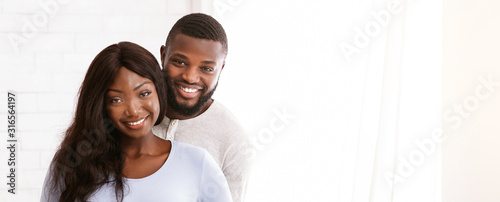 Obraz Cheerful young married couple posing over white background - fototapety do salonu