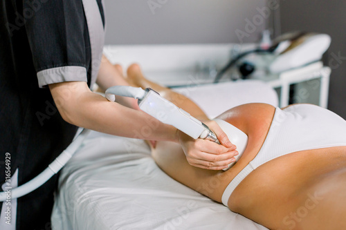 Photo Female doctor cosmetologist doing roller massage with apparatus on female client thighs, close up