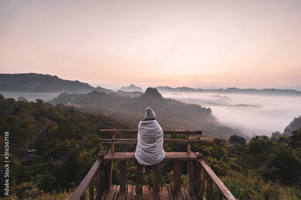 Fototapeta Young woman traveler looking at sea of mist and sunset over the mountain