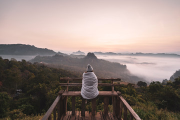 Young woman traveler looking at sea of mist and sunset over the mountain