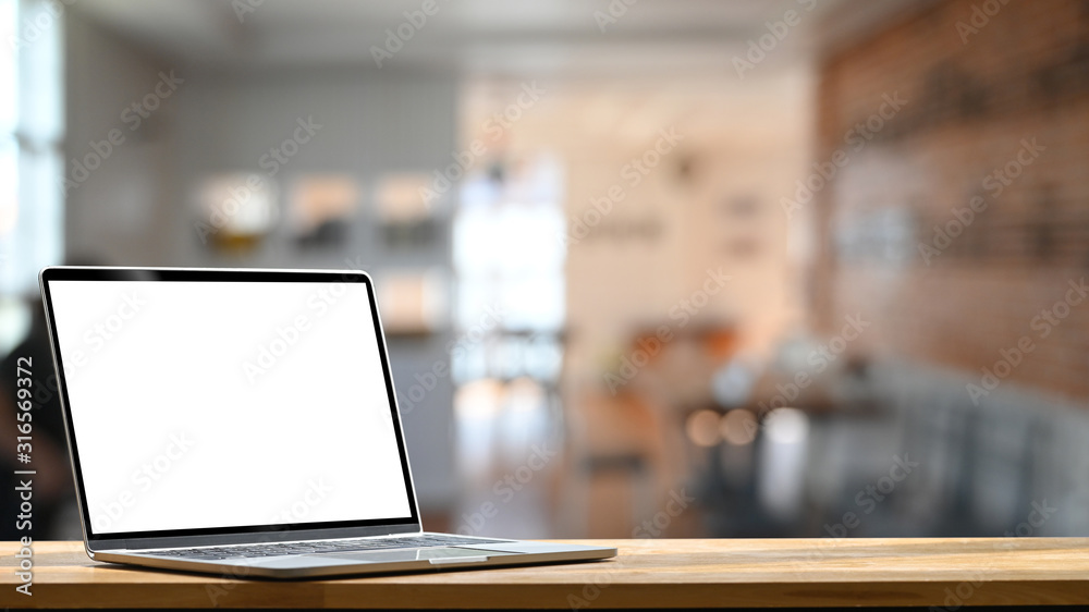 Fototapeta Photo of modern laptop with white blank screen display setting on the wooden table over the blurred modern room.
