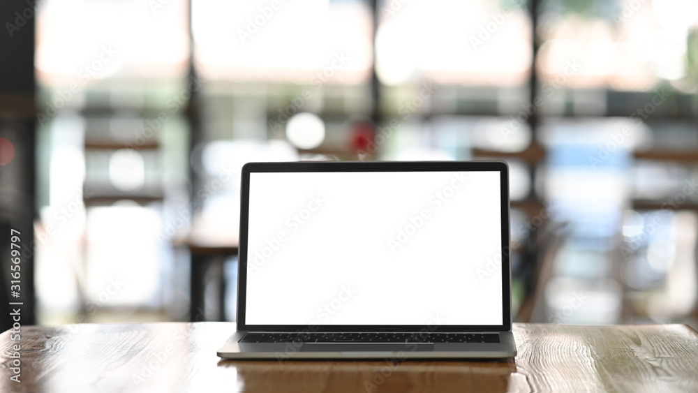 Fototapeta Front shot of modern laptop with white blank screen display setting on the wooden table over the blurred modern cafe.