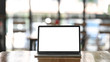 Front shot of modern laptop with white blank screen display setting on the wooden table over the blurred modern cafe.