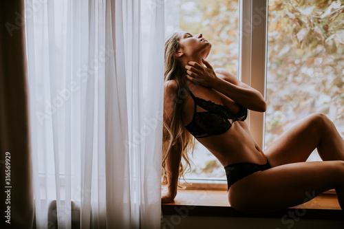 Fotografie, Obraz Beautiful young woman in lingerie sitting and looking outside the window in beau