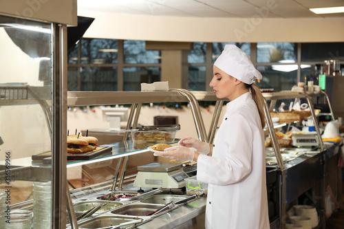 School canteen worker at serving line. Tasty food Wallpaper Mural