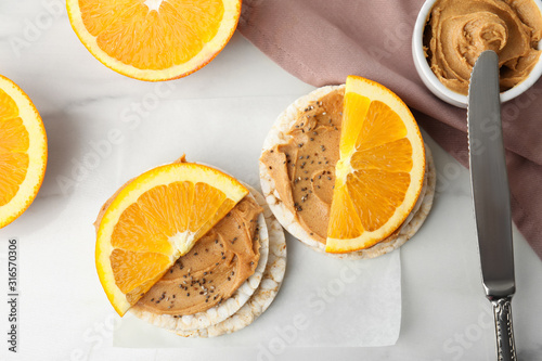 Fotografía  Puffed rice cakes with peanut butter and orange on white marble table, flat lay