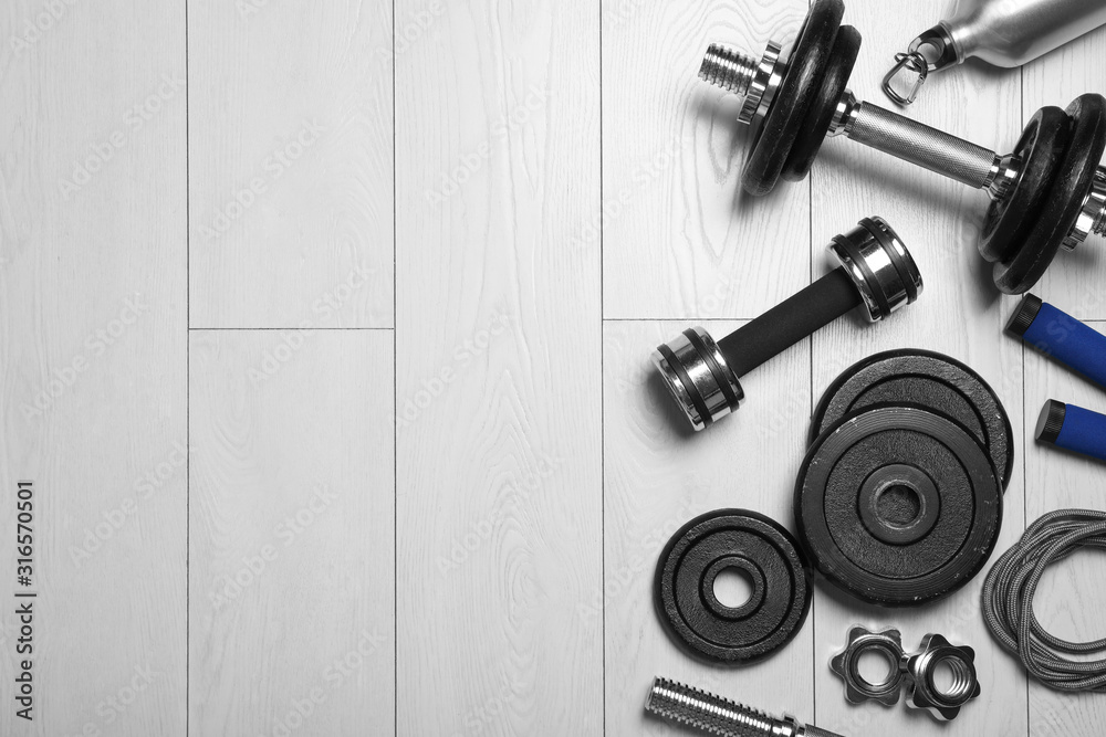 Fototapeta Gym equipment on wooden floor, flat lay. Space for text