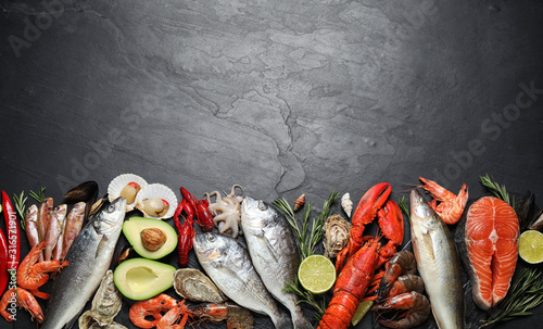 Fotografiet Fresh fish and different seafood on black table, flat lay