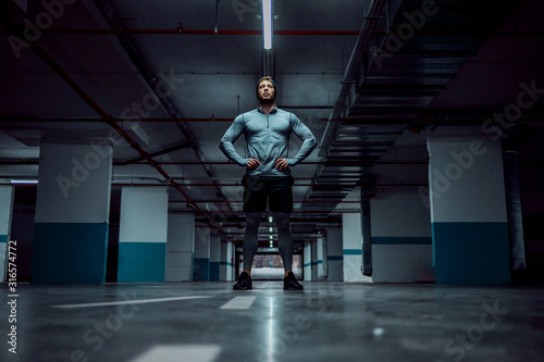 Low angle view of fit handsome caucasian sportsman in active wear standing in underground garage with hands on hips Canvas