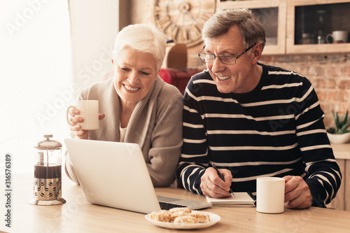 Obraz Cheerful senior couple watching news on laptop online at kitchen - fototapety do salonu