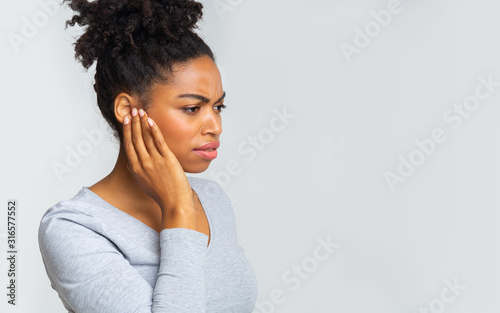 Fototapeta Afro girl suffering from otitis, rubbing her inflamated ear obraz