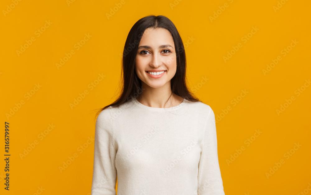 Fototapeta Portrait of beautiful arabic girl smiling while posing over yellow background
