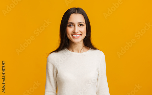 Portrait of beautiful arabic girl smiling while posing over yellow background