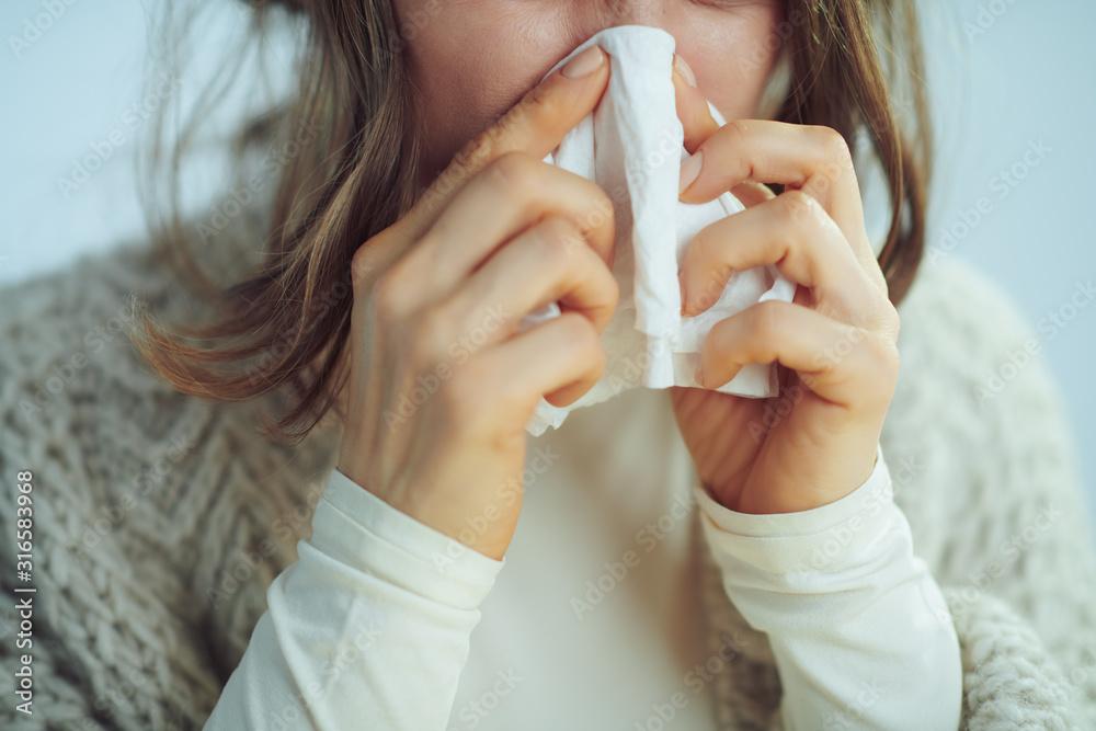Fototapeta Closeup on ill elegant woman wiping nose with napkin