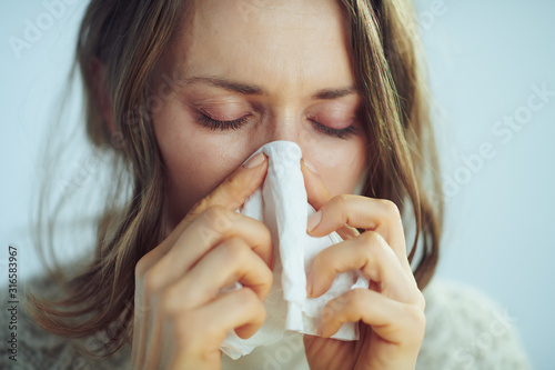 Obraz ill elegant middle age housewife wiping nose with napkin - fototapety do salonu