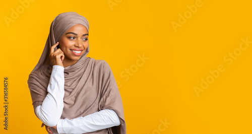 Cuadros en Lienzo Interested black muslim girl looking away at copy space on yellow background