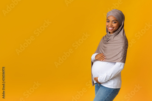 Portrait of pregnant afro muslim woman in headscarf embracing her belly Canvas Print