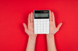 Leinwanddruck Bild - Hands holds a calculator isolated on red background