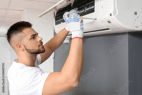 Obraz Male technician repairing air conditioner indoors - fototapety do salonu