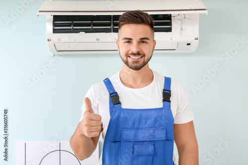 Photo Male technician showing thumb-up after repairing air conditioner