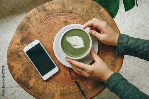 Fototapeta View from above. Girl holds in her hand a cup with fragrant fresh and healthy green matcha latte tea on a wooden table. Nearby lies a cell phone. obraz