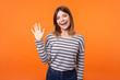 Leinwandbild Motiv Hello! Portrait of adorable friendly woman with brown hair in long sleeve shirt standing waving hand, looking at camera with engaging toothy smile. indoor studio shot isolated on orange background