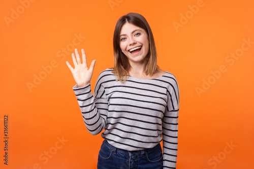 Obraz na plátne Hello! Portrait of adorable friendly woman with brown hair in long sleeve shirt standing waving hand, looking at camera with engaging toothy smile