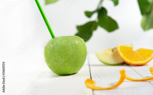 Sliced green apples with straws for juice with leavs and fruit slices on white wooden background, consept freshness and vitamins. Front view.