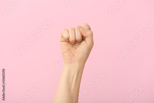 Canvastavla Hand of woman with clenched fist on color background